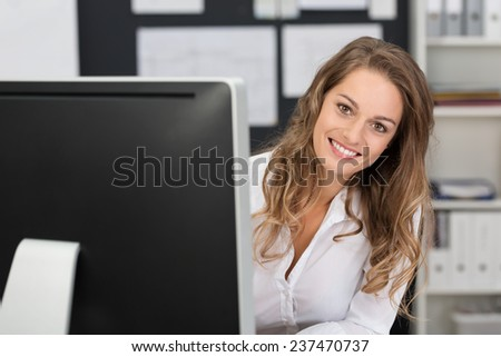 Close up Pretty Smiling Blond Office Woman, with Blond Hair, in White Shirt Peeking Behind Computer at the Office. - stock photo