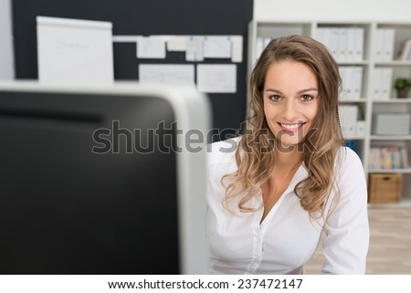 Close up Pretty Smiling Office Woman in White Long Sleeve Shirt, with Long Blond Hair, Looking at the Camera While at her Worktable. - stock photo