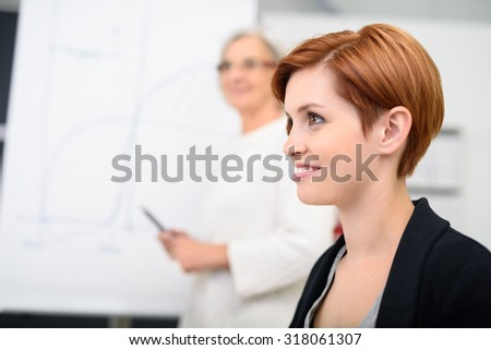 Close up Pretty Young Office Woman In a Meeting Looking Into the Distance with Happy Facial Expression. - stock photo