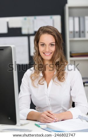 Close up Pretty Young Office Woman Sitting at her Worktable while Smiling at the Camera - stock photo