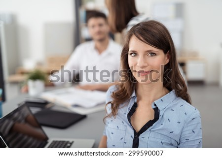Close up Pretty Young Office Woman Sitting Inside the Boardroom with her Laptop on the Table and Smiling at the Camera. - stock photo