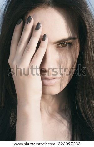 Close up Pretty Young Woman Covering her Half Face with Hand and Looking Fierce at the Camera. - stock photo