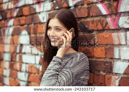 Close up Pretty Young Woman in Gray Tops Calling Someone Through Mobile Phone While Leaning on Brick Wall. - stock photo