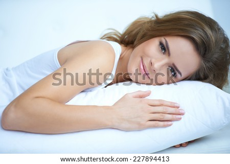 Close up Pretty Young Woman Laying Prone on White Pillow While Looking at the Camera. - stock photo