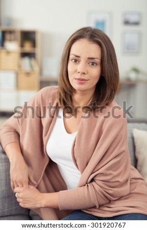 Close up Pretty Young Woman Sitting on a Couch in the Living Room and Looking at the Camera with Charming Smile. - stock photo