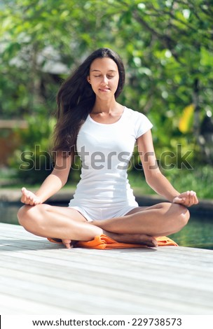 Close up Pretty Young Woman with Long Black Hair Doing Lotus Yoga at the Poolside With Closed Eyes. A Health and Wellness Concept. - stock photo