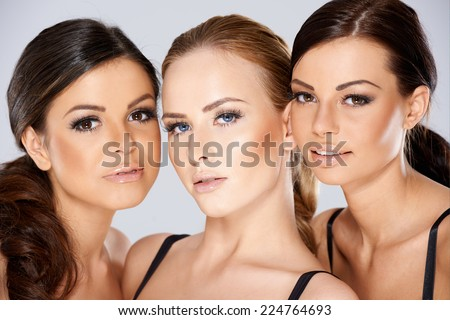 Close up Pretty Young Women Faces  Looking at Camera. Captured in Studio on Gray Background. - stock photo