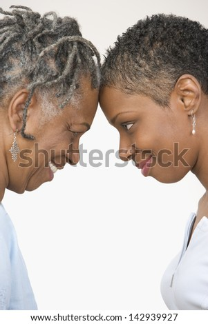 Close up profile of mother and daughter touching forehead - stock photo