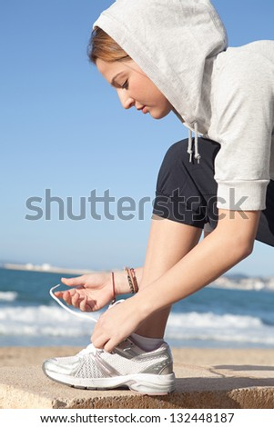 Close up profile portrait of a young sports woman doing up her trainers shoe laces against an intense blue sky by a golden beach. - stock photo