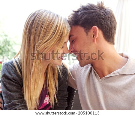 Close up profile portrait of an attractive young tourist couple on holiday being romantic and kissing while relaxing during a summer break vacation. Love and relationships outdoors. - stock photo
