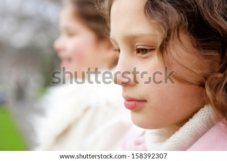 Close up profile portrait of two girl children sisters together in a park during a cold winter day, wearing warm coats  and being thoughtful, outdoors. - stock photo