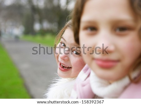 Close up profile portrait of two girl children sisters together in a park during a cold winter day, wearing warm coats  and turning to smile joyfully at camera, outdoors. - stock photo