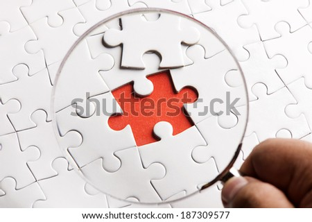 CLOSE UP-Puzzle pieces with a magnifying glass. Concept image of detecting a defect. - stock photo