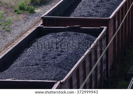 Close-up railroad tracks with wagons with coal on summer day - stock photo