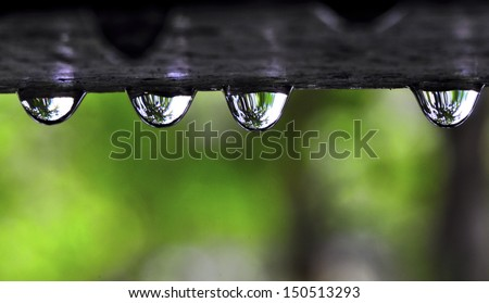 close up rain drop from roof in the garden with green background - stock photo
