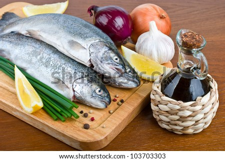 close-up raw fish trout with peppers, onions and lemon on a wooden board - stock photo
