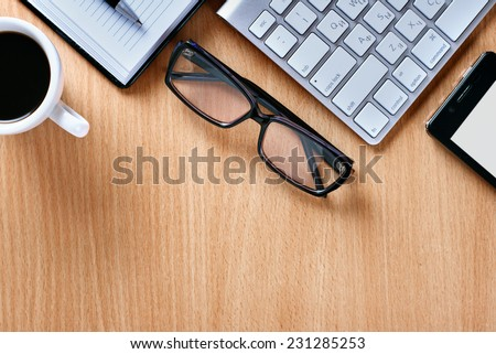 Close up Reading Eye Glasses on Businessman Wooden Table with Other Stuffs - Coffee, Keyboard, Notebook, Pen and Phone. - stock photo