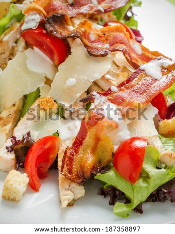 Close-up restaurant shot of rich and tasty caesar salad including lettuce, tomato, croutons, grilled chicken, grilled bacon, parmesan strips and sauce - stock photo