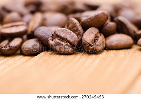 Close-up roasted coffee beans on a old wooden table - stock photo