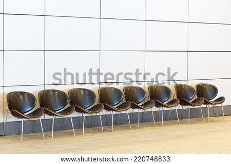 Close up row of waiting chairs and white color wall in office building - stock photo