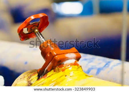 close up rust on old red 45 �° Ammonia valve on yellow pipe. - stock photo