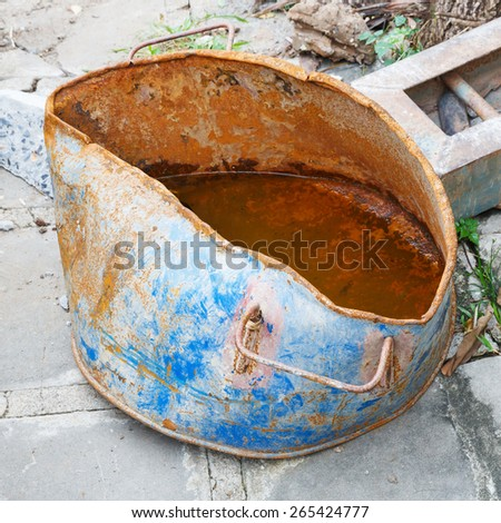 Close up rusty and distorted steel bucket in construction site - stock photo
