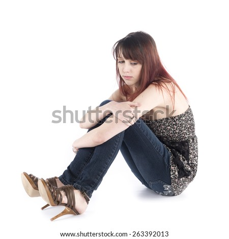 Close up Sad Young Woman in Trendy Fashion Sitting on the Floor While Embracing her Knee, Isolated on White Background. - stock photo