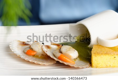 Close up Scallop seafood appetizer with spinach sauce, polenta and spices - stock photo
