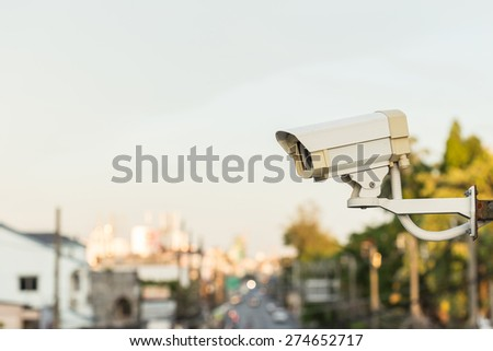 Close up Security CCTV camera operating over the road - stock photo