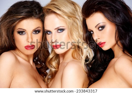 Close up Seductive Young Women with Long Wavy Hair and Wearing Tube Tops  Looking at Camera. Captured in the Studio. - stock photo
