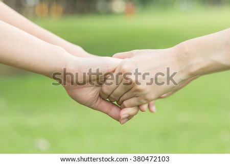 close up/selective focus of couple women take hands holding together for helping and cheer up:giving/supporting/encourage/care/love concept:family and friends concept.happy/hope/trust:girl handshake. - stock photo