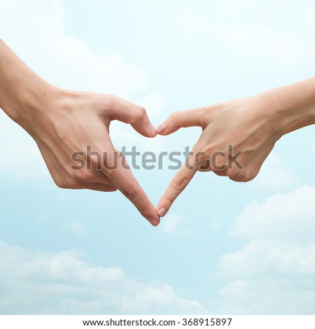 close up/selective focus on man/woman hand make heart shape on blurred soft bright vivid blue cyan nature sky and cloud background:love of people conceptual:happy good healthy living concept.take care - stock photo
