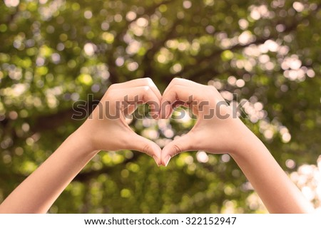 close up selective focus on woman hands make heart over blurred natural tree forest background at outdoor park:heart shape form for good living happy life concept.picture with instagram filter effect. - stock photo