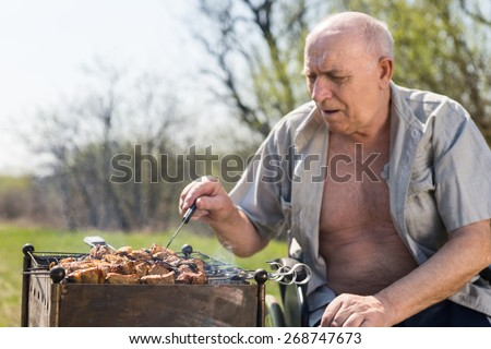 Close up Senior Man with Open Shirt Sitting on his Wheelchair While Grilling Some Food to Eat Outside on a Very Sunny Day. - stock photo