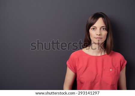 Close up Serious Adult Woman in Casual Red Shirt Against Gray Wall Background with Copy Space, Looking at the Camera. - stock photo
