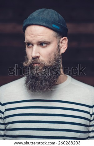 Close up Serious Handsome Guy with Long Beard, Wearing Casual Stripe Shirt and Bonnet, Looking to the Left of the Frame. - stock photo