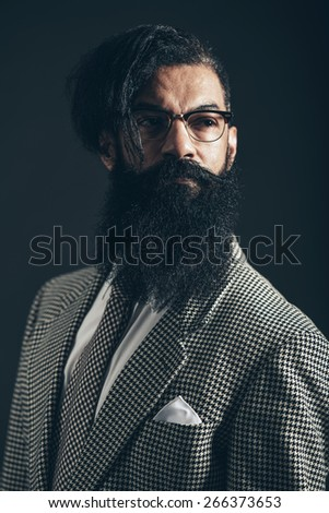 Close up Serious Man with Long Beard and Mustache, Wearing Formal Checkered Suit, Looking to the Right of the Frame on a Black Background. - stock photo