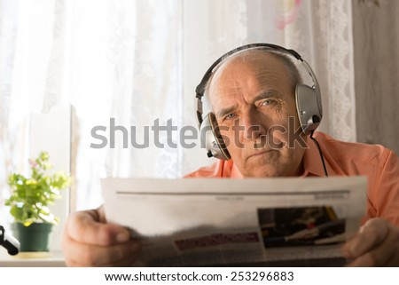 Close up Serious Old Age Man with Headset Holding Newspaper While Staring at the Camera. - stock photo