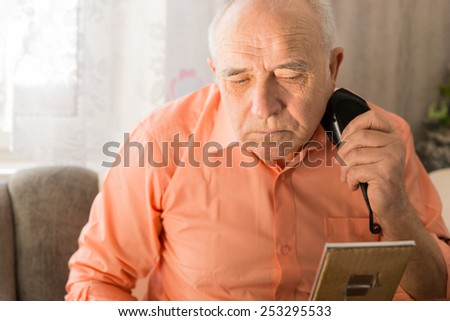 Close up Serious Old Man Shaving Beard with Electric Razors While Facing Small Mirror on the Table. - stock photo