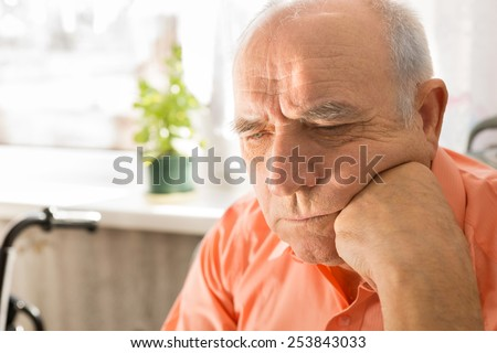 Close up Serious Senior Bald Man, in Orange Shirt, Looking Down with Fist on his Face - stock photo