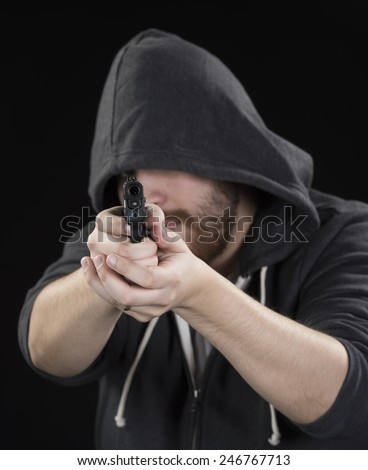 Close up Serious Young Man in Black Hood Holding Gun on Black Background. Emphasizing Crime Concept - stock photo