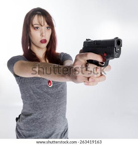 Close up Serious Young Woman in Gray Shirt Holding a Hand Gun with her Both Hands, Isolated on White Background. - stock photo