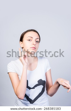 Close up Serious Young Woman Pointing Up and Down Against Gray Background While Looking at the Camera. - stock photo