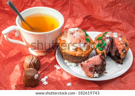 Close up set of colorful cupcakes with cup of tea on red - stock photo