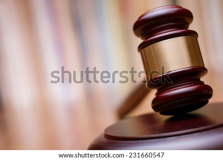 Close up Shiny Wooden Law Gavel in Dark Brown Color, on Top of Wooden Table at the Office. - stock photo
