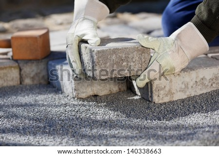 Close up shit of construction worker paving the brick road - stock photo