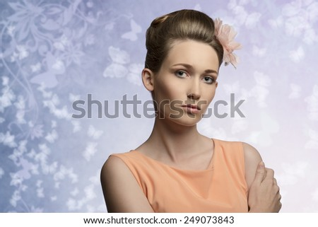 close-up shoot of very beauty woman with perfect skin and fresh look, elegant floral hairdo and orange dress  - stock photo