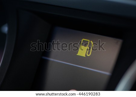 Close up shot of a car's dashboard with the fuel icon lit. - stock photo