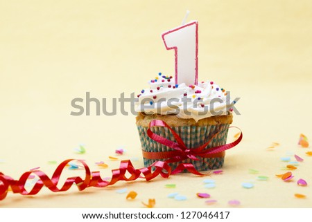 Close-up shot of a cupcake with number 1 candle tied with red streamer over plain yellow background. - stock photo