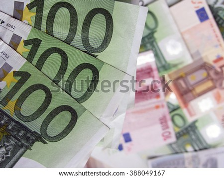 Close up shot of a few 100-Euro money notes with a pile of cash in background. - stock photo